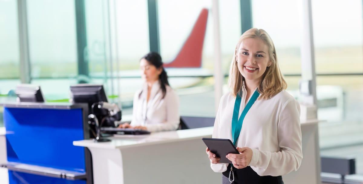auxiliar de vuelo en aeropuerto atendiendo a pasajeros