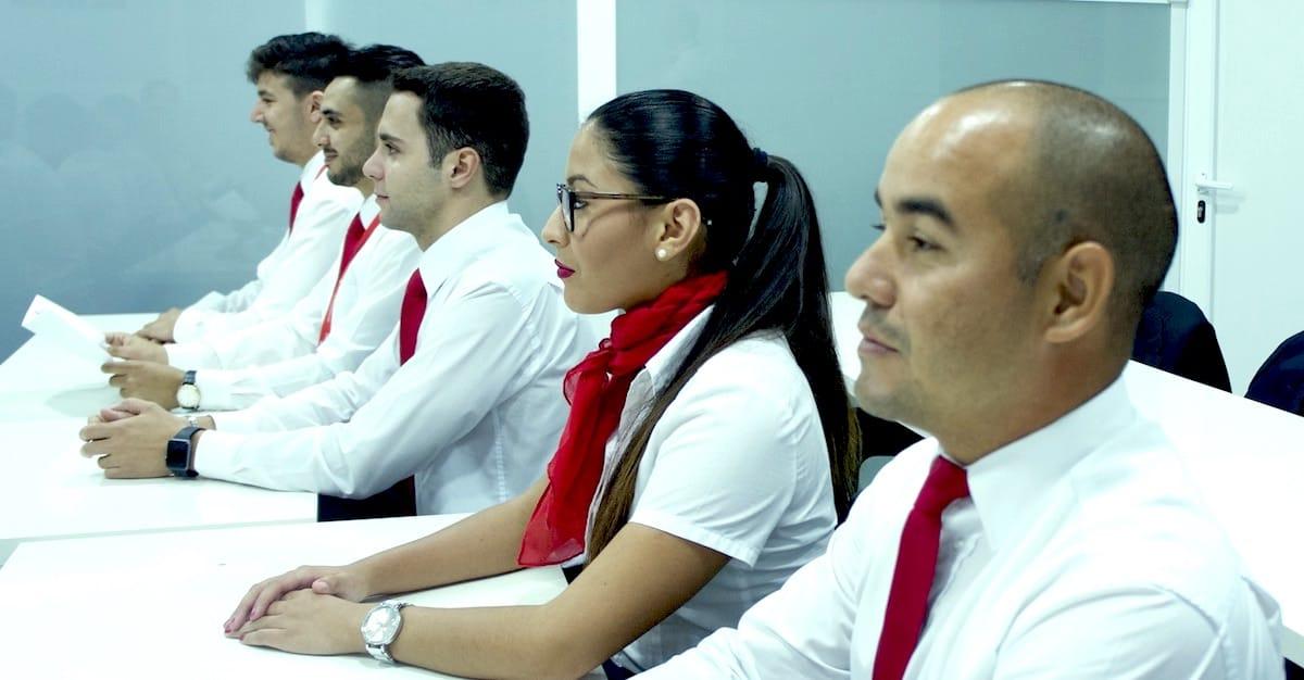 Varias personas uniformadas y sentadas en posición erguida