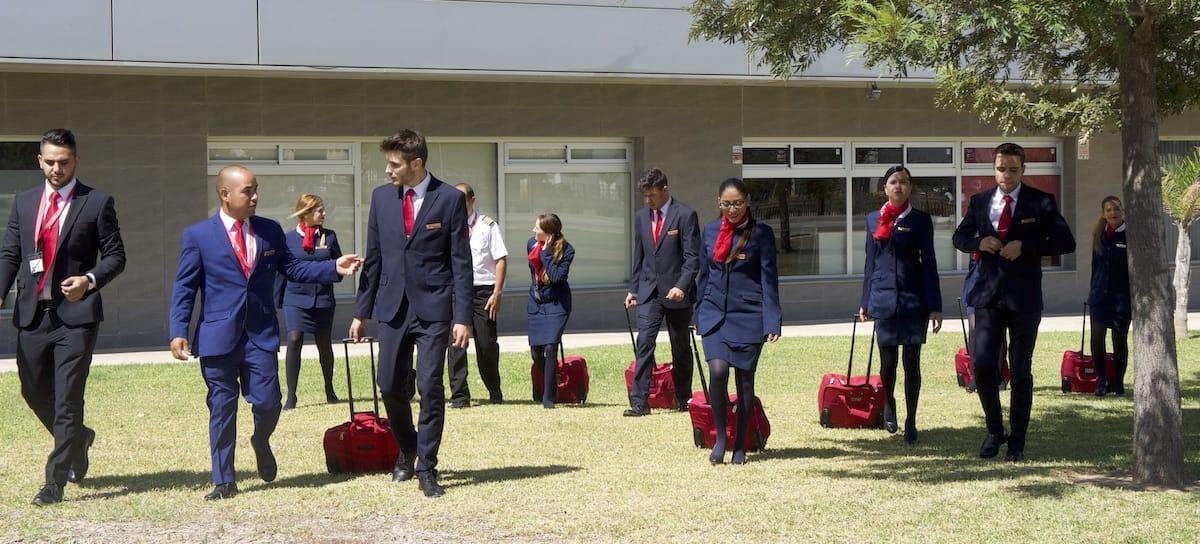 Estudiantes del Curso Azafata de Vuelo de Air Hostess Málaga caminando por la hierba con uniforme y maleta.