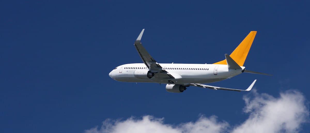 Avión de pasajeros en vuelo sobre cielo azul con nubes.