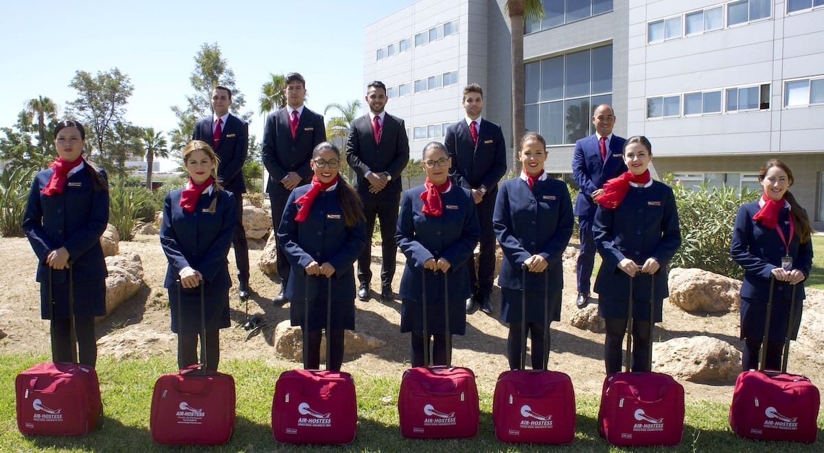 Promoción de alumnos de Air Hostess Málaga uniformados y con maleta.