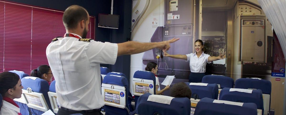 Instructor de academia Air Hostess Málaga practicando la señalización con alumna.