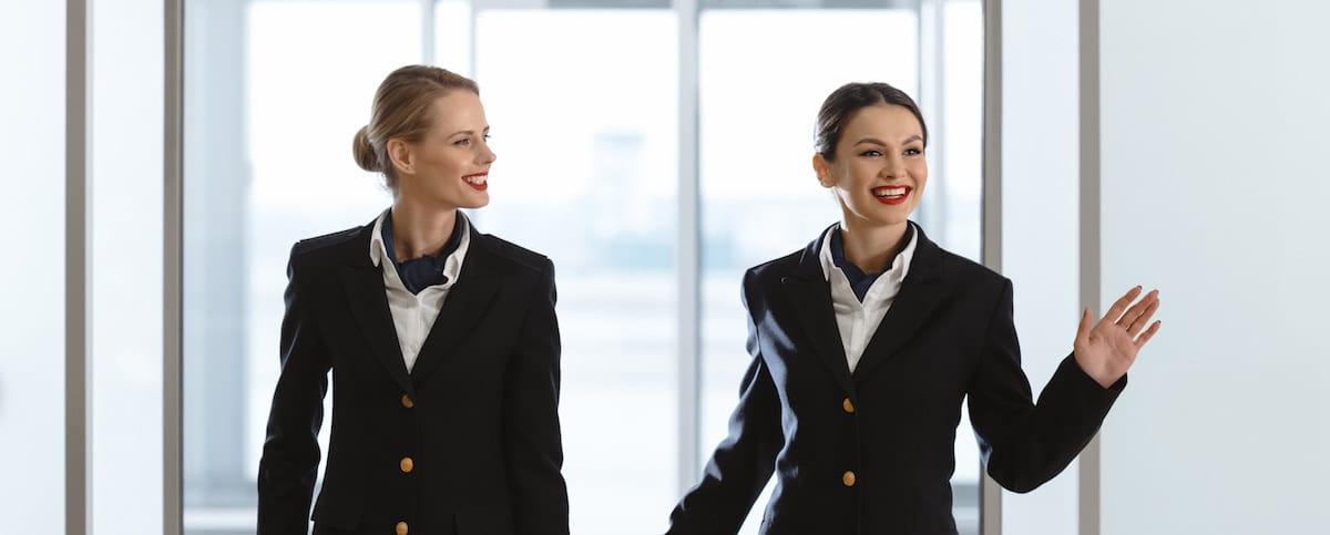Azafatas con uniforme sonriendo.