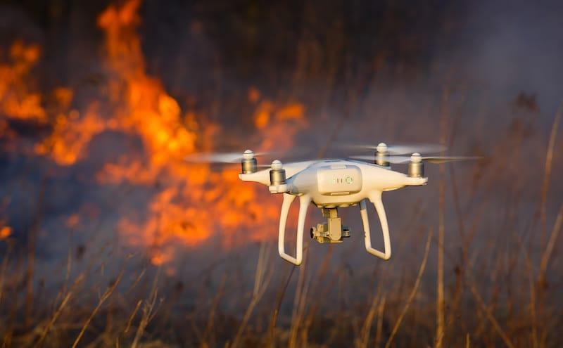 Dron volando sobre un incendio para controlar avance de las llamas.