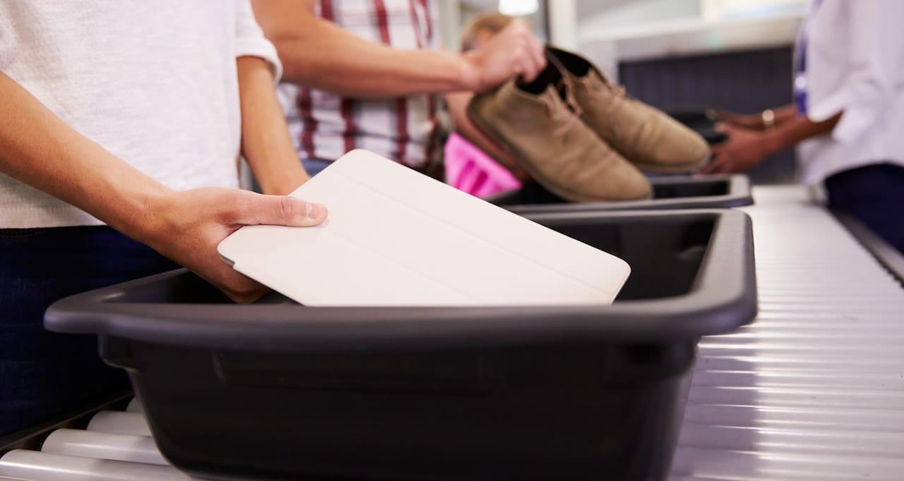 Pasajeors dejando sus pertenencias en la cinta transportadora en el control de salidas del aeropuerto.