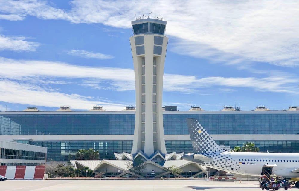 Vista exterior de la torre de control del Aeropuerto de Málaga (AGP) con avión comercial a un lado.