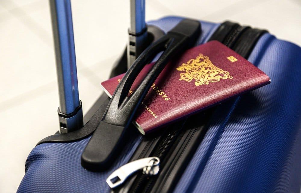 Maleta de mano y pasaporte para viajar en avión.