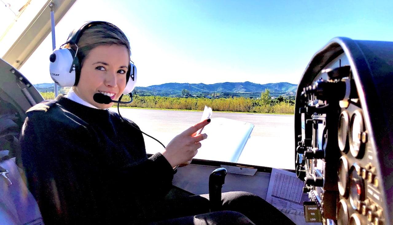 Alumna de One Air revisando manual antes de despegar.